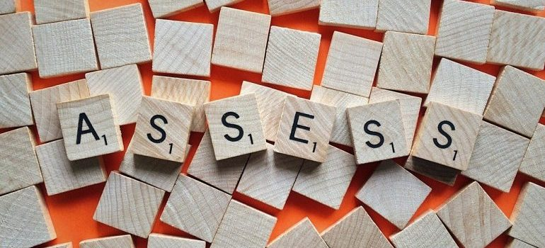 Cubes spelling the word assess.
