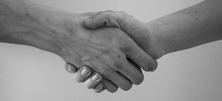 A handshake after choosing moving services Northern VA.