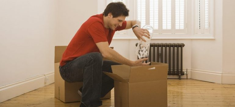 Man unpacking boxes in new home
