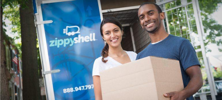 a couple holding a moving box