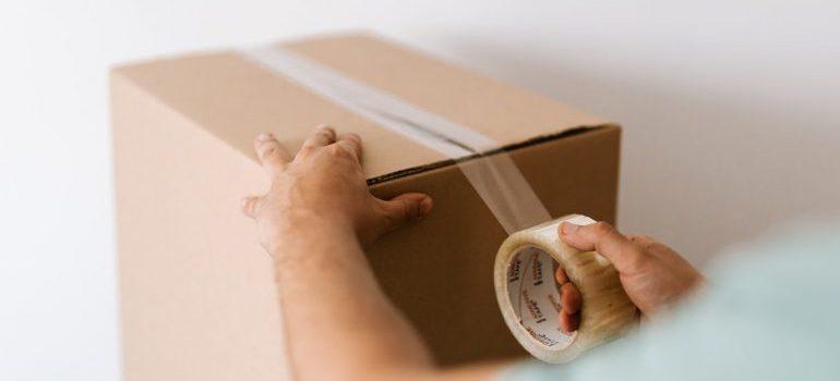 man taping a moving box