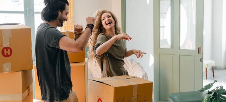 Happy couple unpacking boxes and dancing