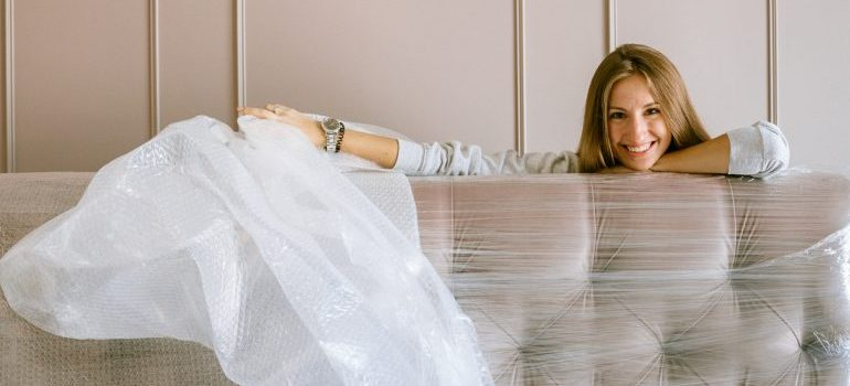 A woman wrapping a couch in protective wrapping.