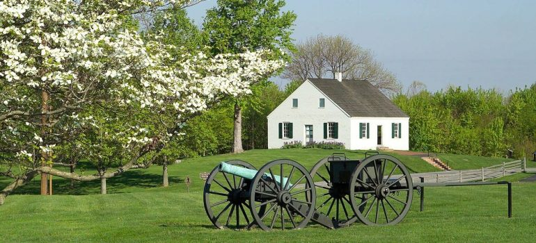 a home in a green pasture with two historical cannons in front of it
