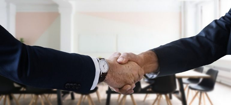 two people shaking hands after finishing a job interview as an important factor to look for when moving from Rockville to Bethesda