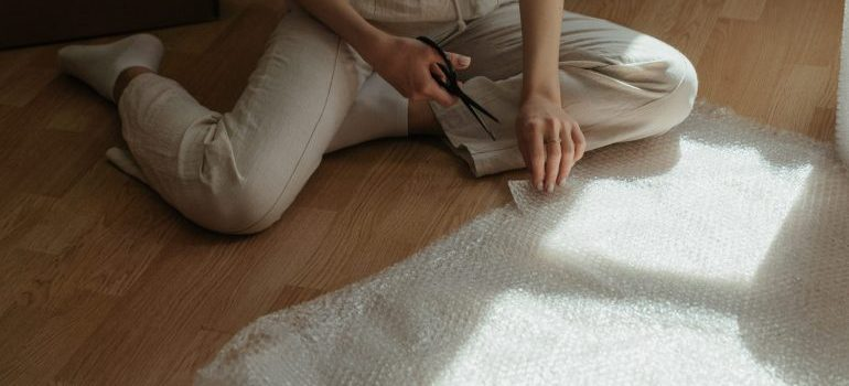 Woman sitting on the floor and cut plastic wrap