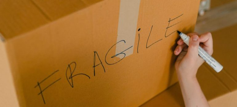 """moving box with """"fragile"""" writing on it"""
