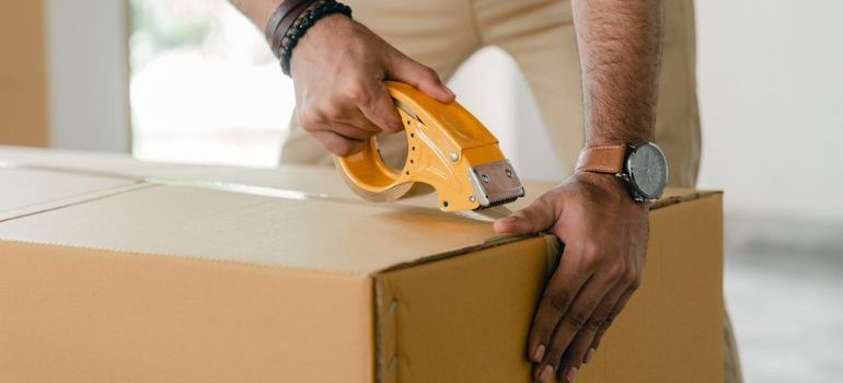 A man taping up a cardboard box, representing work done by moving and storage Gainesville experts.
