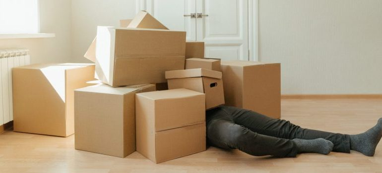 person laying on the floor covered with moving boxes