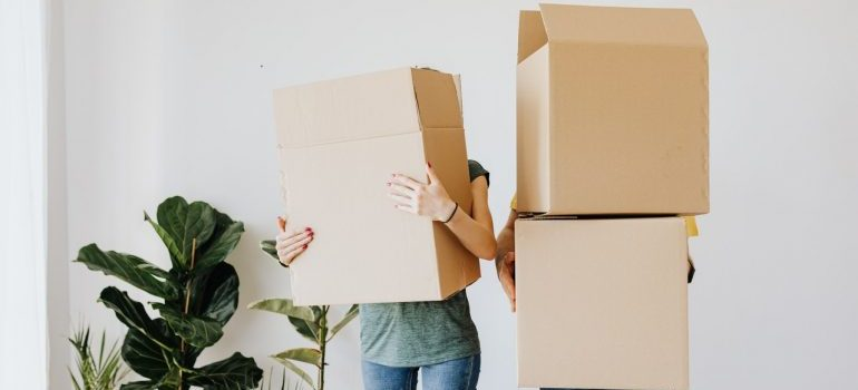 a couple holding moving boxes