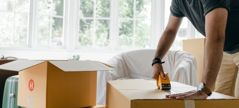 Picture of a man taping a box