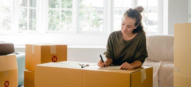 a woman labeling a moving box