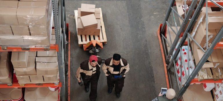 two men in a storage unit organizing some items as an activity you should do when you check on your DMV storage unit