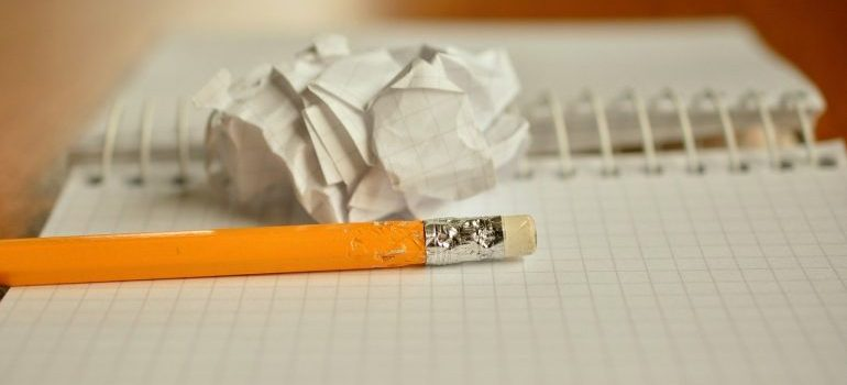 A pen and a crumpled piece of paper near a notebook.