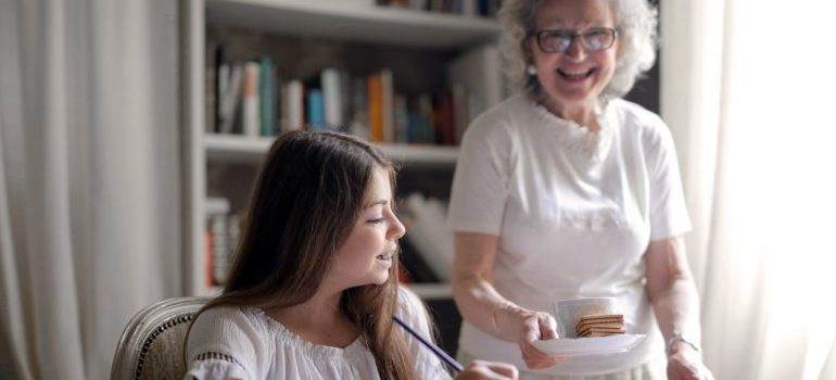 Picture of an older woman with her granddaughter. If you want to put our decluttering tips for seniors into practice, you should ask your family members for help