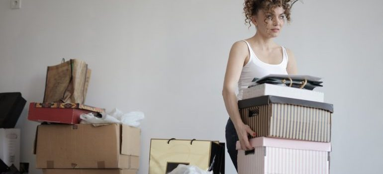 A picture of a woman decluttering her home. You should clean your home before we proceed with Northern Virgina home improvement tips