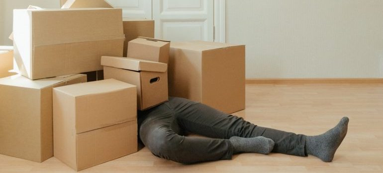 A man laying on the floor under a load of boxes.