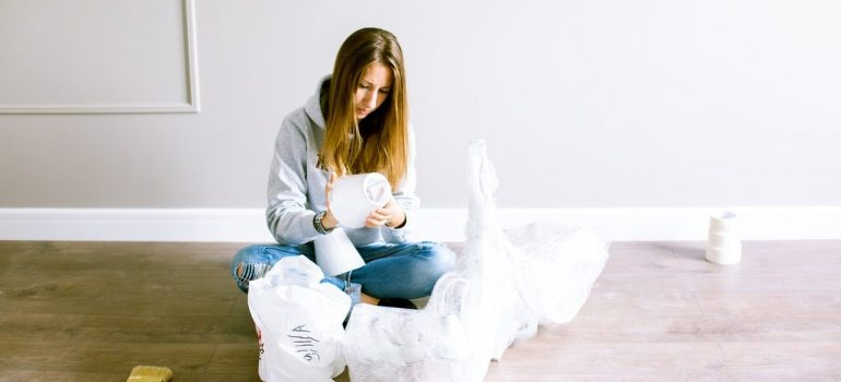 a woman sitting on the floor while packing items in bubble wrap