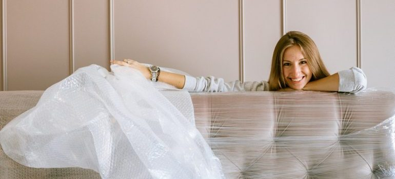 A woman unwrapping her couch.