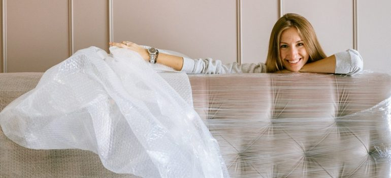 a woman putting bubble wrap before storing couches and armchairs