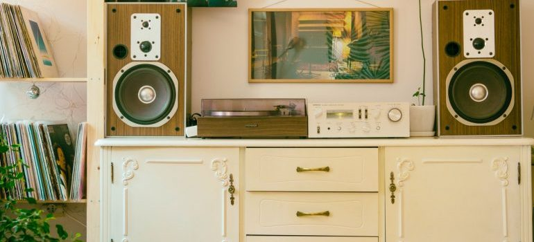 White vintage furniture with a stereo and family pictures on it.