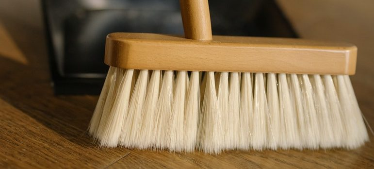 A person suing a broom to clean floors