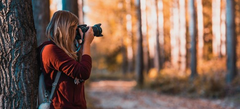 A girl holding a DSLR camera in the woods taking pictures.