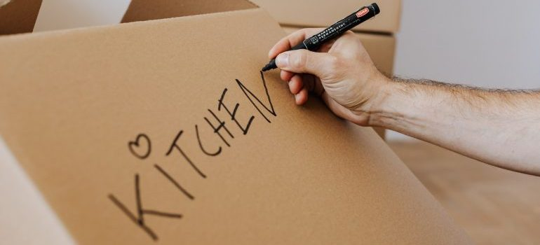 Picture of a man writing on the box. One of the most essential packing tips is - never forget to label your boxes