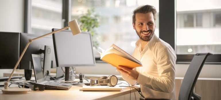 A man smiling while sitting at his desk