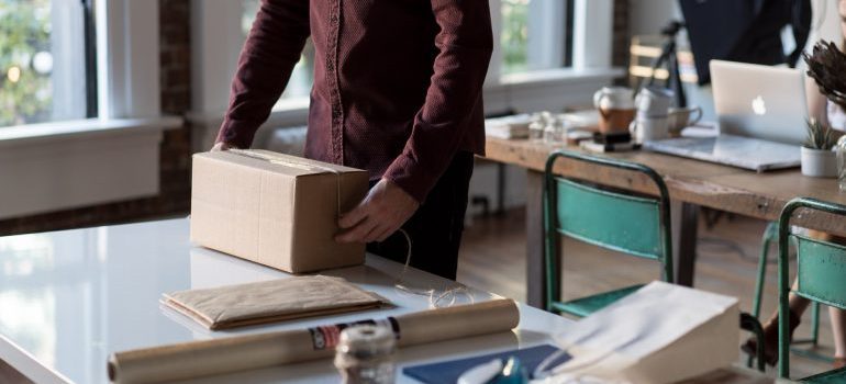 A guy packing his items into boxes