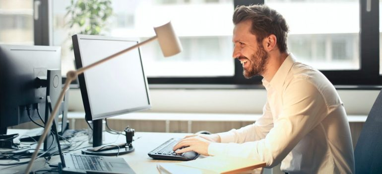a man in a white shirt laughing while looking at the computer screen in his office