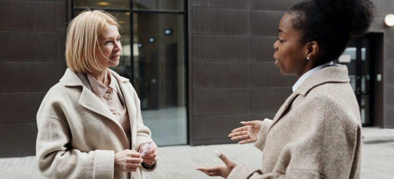 two women in coats talking outside of a building