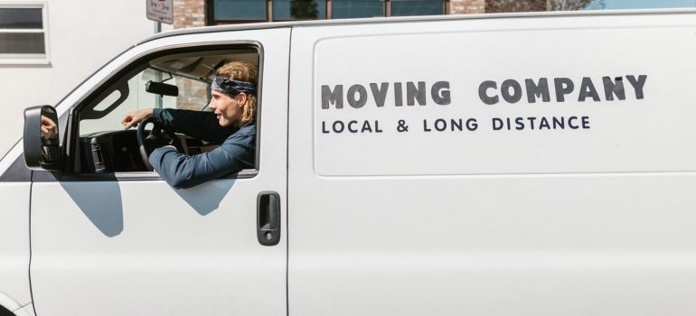 """a man sitting behind the wheel of a white van that says """"Moving Company"""""""