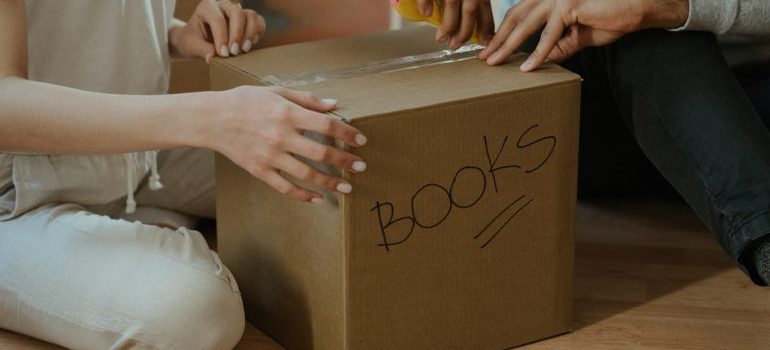 A family opening a moving box with books